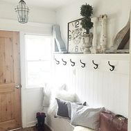 Upholstered farmhouse entryway bench with pillows; rustic shelf and coat wall hooks